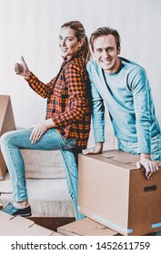 Happy couple with cardboard boxes in new house at moving day. Woman putting thumbs up.