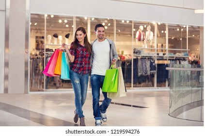 Happy couple carrying bags in shopping