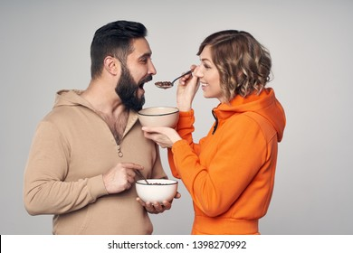 Happy couple in casual clothes eating corn flakes with milk . woman feeding a man