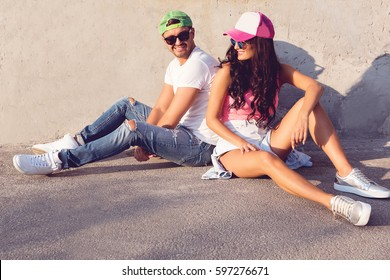 happy couple in the casual urban style seating on the street have fun and joy the summer day