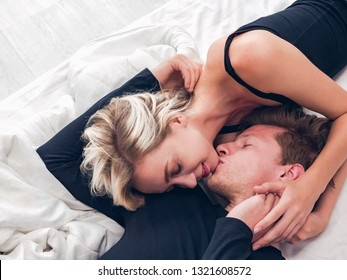 Happy couple caucasian in love hug and kiss each other on bed in bedroom, People lifestyles concept.
