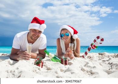 Happy couple celebrating Christmas on beach