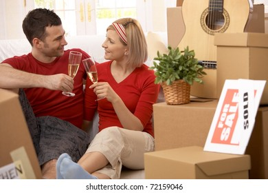 Happy couple celebrating moving to new house with champagne.?