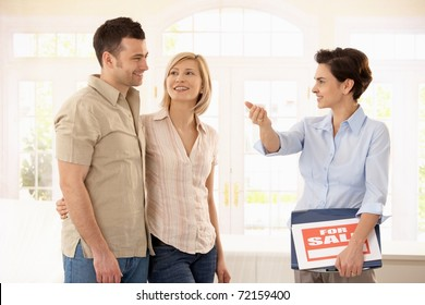 Happy couple checking new house with estate agent.?
