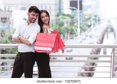 Happy couple cheering after a hard day of huge sale shopping in asian country. Young handsome white male and beautiful asian female with red shopping bag looking very satisfy. Apply urban looks.