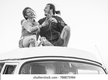 Happy couple cheering with beers on top of roof minivan - Travel couple having fun on road trip vacation  - Love, van lifestyle  and holidays concept - Focus on hands bottles - Black and white editing