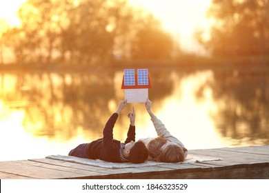 Happy couple of children dreaming of a house with solar panels. Solar energy panel concept. Alternative energy.