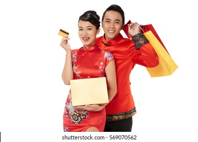 Happy couple in Chinese traditional costumes with presents and credit card