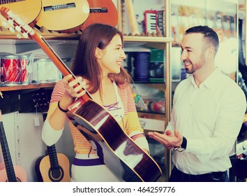 Happy couple choosing acoustic guitar in music instruments shop