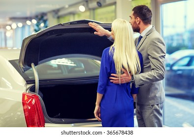 happy couple choosing car in auto show or salon