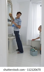 Happy couple cleaning bathroom while looking at each other