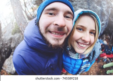 happy couple climbers walks under the cliff at winter and looks at the camera with funny faces. photographed on fish eye lens