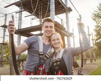 happy couple at climbing park showing climbing carbine for safety