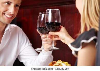 Happy couple clinking glasses of red wine in a restaurant