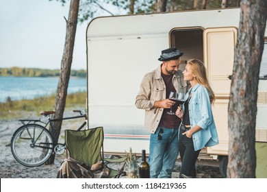 happy couple clinking with glasses of wine and looking at each other near campervan