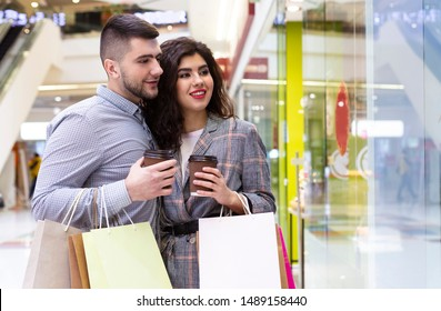 Happy couple with coffee to go and purchases looking at shop window, free space