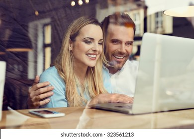 Happy couple at coffee shop looking at laptop