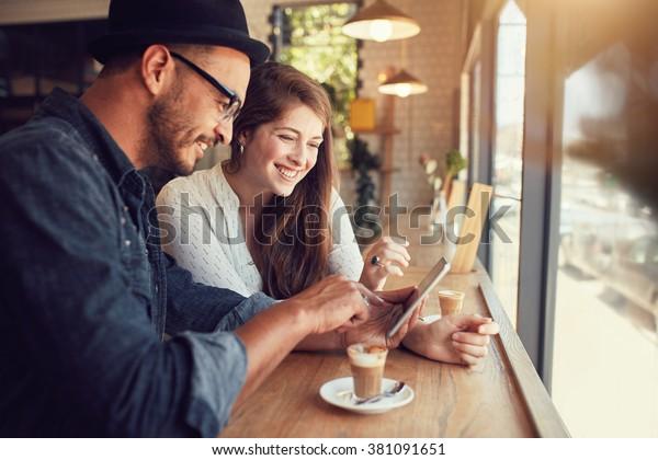 デジタルタブレットでインターネットサーフィンをしている喫茶店で幸せなカップル。レストランでタッチスクリーンのパソコンを見ている若い男女。