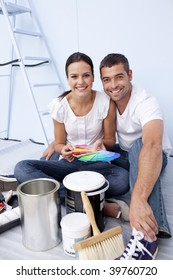Happy couple with color samples to paint new appartment
