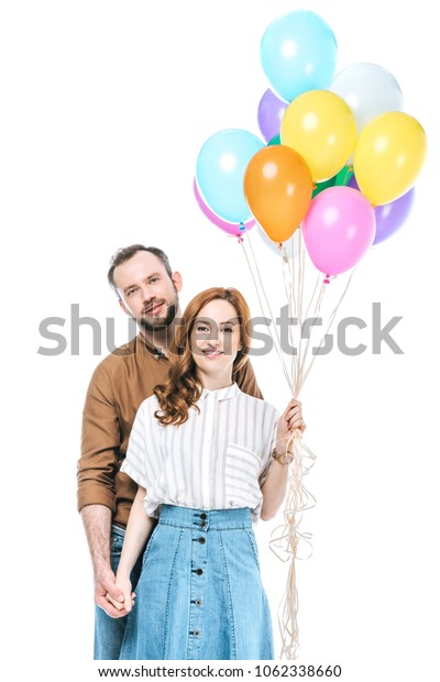 happy couple with colorful balloons smiling at camera isolated on white