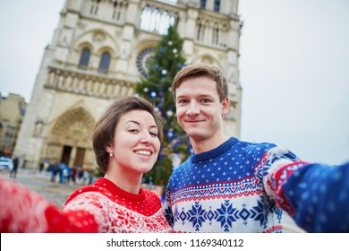 Happy couple in colorful sweaters taking selfie with mobile phone near Notre-Dame cathedral and decorated Christmas tree in Paris, France