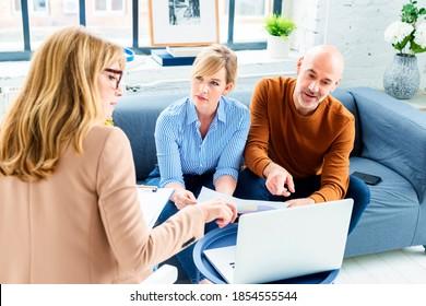 Glückliches Paar, das sich mit seinem Finanzberater in Verbindung setzt, während es zu Hause im Wohnzimmer sitzt.