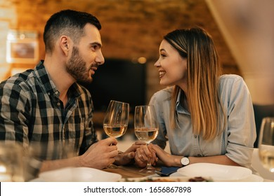 Happy couple communicating while having dinner and drinking wine in dining room.