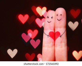 Happy Couple Concept. Two fingers in love with painted smiley faces and heart over bokeh background