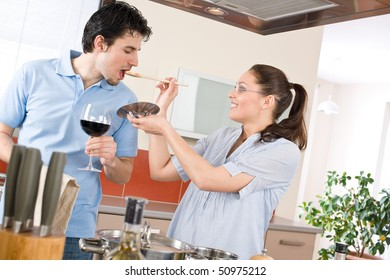 Happy couple cook together in modern kitchen tasting food, drink red wine
