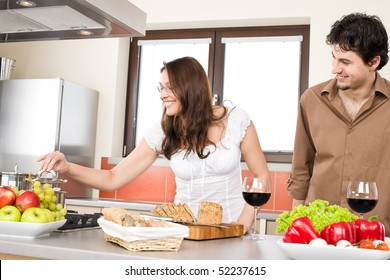 Happy couple cook together in modern kitchen, drink red wine