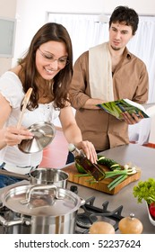Happy couple cook together in modern kitchen with cookbook