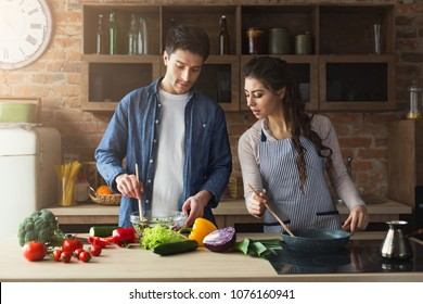 Happy couple cooking healthy dinner together in their loft kitchen at home. Preparing vegetable salad.