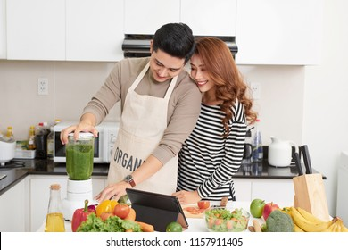 Happy couple cooking in kitchen. Man and woman happy on kitchen cooking.