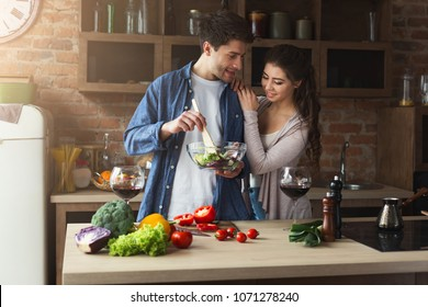 Happy couple cooking and tasting healthy food in their loft kitchen at home. Woman and man drinking wine. Preparing vegetable salad.