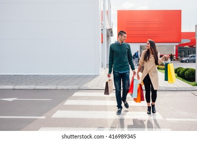 Happy couple crossing the street with shopping bags at sunset