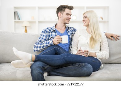 The happy couple with a cup relax on the sofa