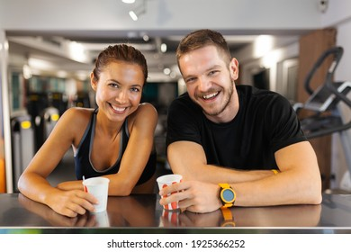 happy couple with cups of coffee resting in a fitness club