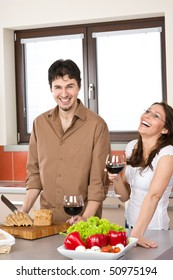 Happy couple cut bread in modern kitchen together and drink red wine