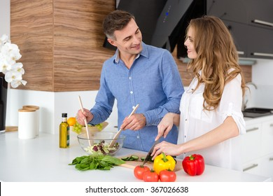 Happy couple cutting vegetables and making salad on the kitchen together