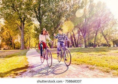 happy couple cycling in park, smiling and having fun riding bicycles in colorful autumn in park