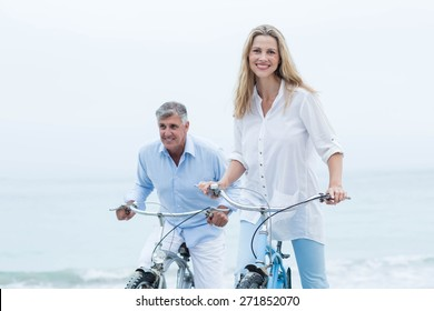 Happy couple cycling together at the beach