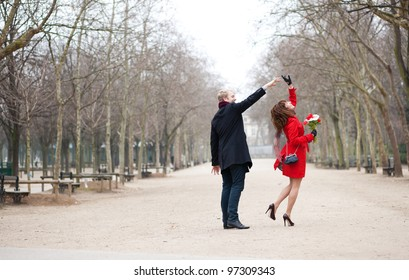 Happy couple dancing in the Luxembourg garden of Paris