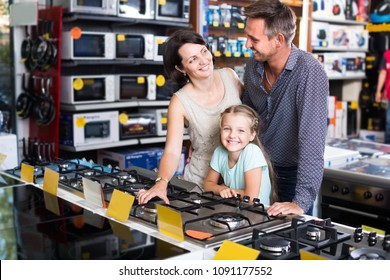 Happy couple with daughter buying new gas-stove in home appliance hypermarket