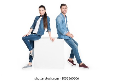happy couple in denim leaning on white cube, isolated on white
