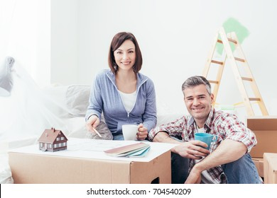 Happy couple designing their new house, they are checking the house project together and doing home renovations