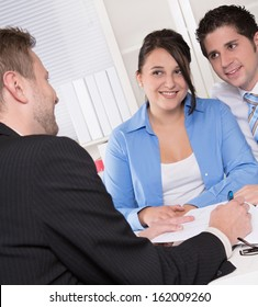 Happy couple discussing future financial plans with consultant