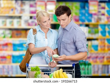 Happy couple discussing the shopping list and chosen products standing near the cart full of food