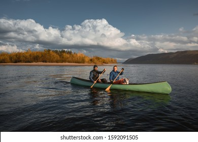 Happy couple with dog  in canoe at sunset.