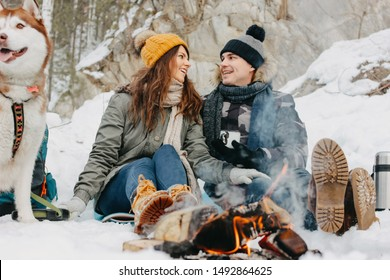 The happy couple with dog haski at the forest nature park in the cold season. Travel adventure love story