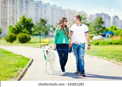 Happy couple with a dog having fun outdoors in the city